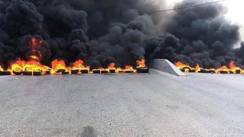 بالصور: عناصر ارسلانية مسلحة تقطع الطريق الدولي في بعلشميه بالاطارات المشتعلة